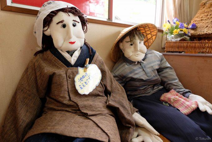 山上駅の片隅で仲良く座る人形