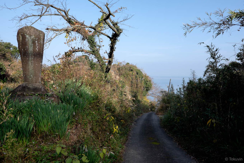 駅から海へと続く坂道と石碑。