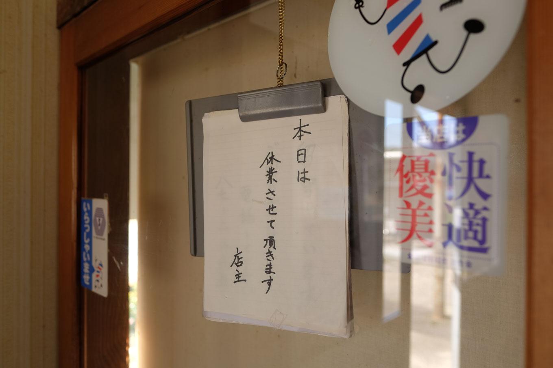 理髪店の出入口に掲げられた本日休業の文字。