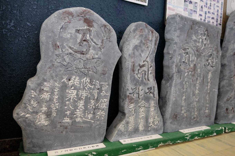 階段の踊り場に並べられた、江ノ河原の自然石板碑を含む複数の石板碑(許可を得て撮影)。