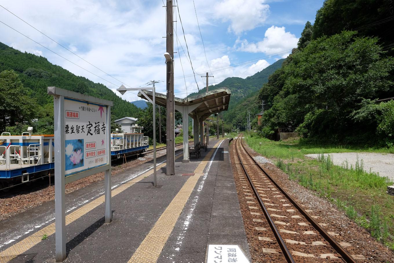 緩やかにカーブする豊永駅ホーム。駅名板より存在感のある大きな定福寺の案内板が立てられている。