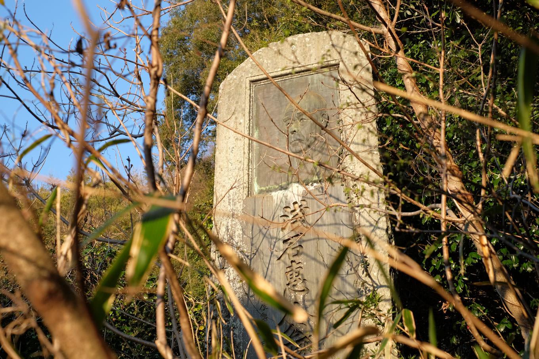 草木に埋もれる浅石恵八の石碑。