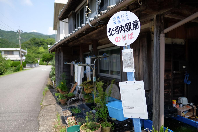 駅前通りの先を横切る、県道脇に立つバス停。