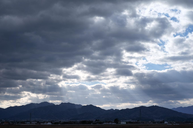 空に広がる黒雲と、雲間から降り注ぐ光条。
